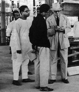 En ung Doshi iklädd svart jacka på en byggarbetsplats med Le Corbusier.