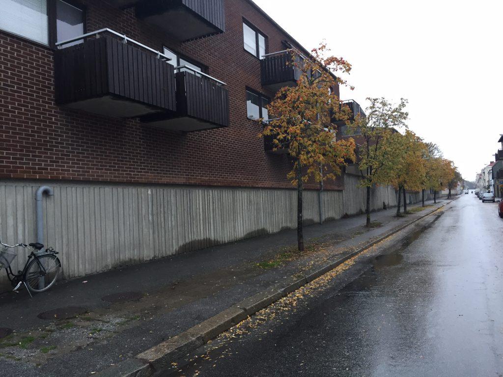 """Möllebacken, Karlshamn, en gatusekvens i folkmun kallad Berlinmuren. Stadsdelen präglas av 1970-talets bilvänliga stadsplanering som i många städer rev hus för att bredda gator och göra det bekvämt för bilen. De nya stadsdelarna som växte fram vände oftast ryggen mot den numera breda och """"farliga"""" gatan, som här i Karlshamn där vi hittar stadens längsta entrélösa fasad. Till följd av avsaknad av entréer upplevs denna gatusekvens av många medborgare som otrygg. Foto: Emina Kovacic"""