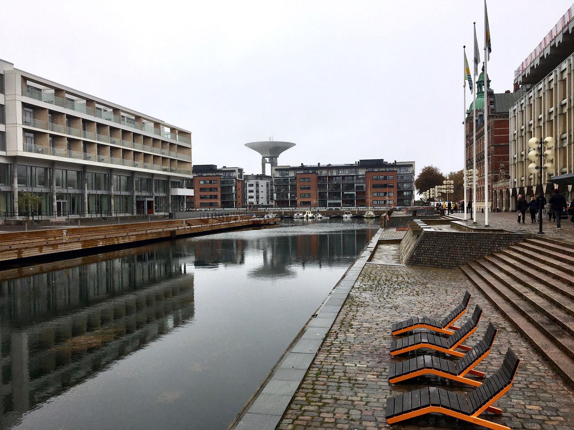 Nytt möter gammalt i Landskrona - lyckad integrering av ny form-, material- och proportionsmässigt anpassad bostadsbebyggelse och hotell i ett centralt och attraktivt läge. Till vänster Hotell Öresund Konferens och Spa samt bostadskomplex ritat av Jais arkitekter, byggnadsår 2018. I fonden den nya stadsdelen Nyhamn, till höger Stadshuset av Sten Samuelsson och Inge Stoltz, byggnadsår 1976, allt vackert inramat med en funktionell och väl gestaltad strandpromenad som ter sig inbjudande även under en grå oktoberdag. Foto: Emina Kovacic